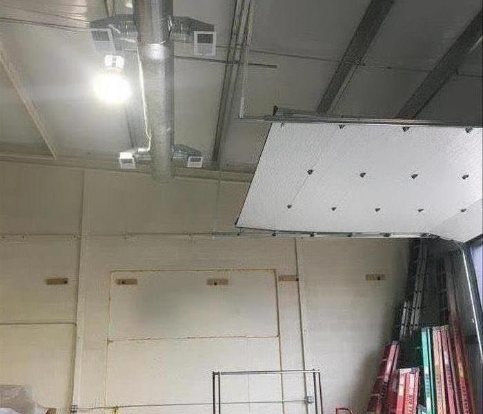 Sparkling clean and freshly painted warehouse ceiling, walls, and bay door.