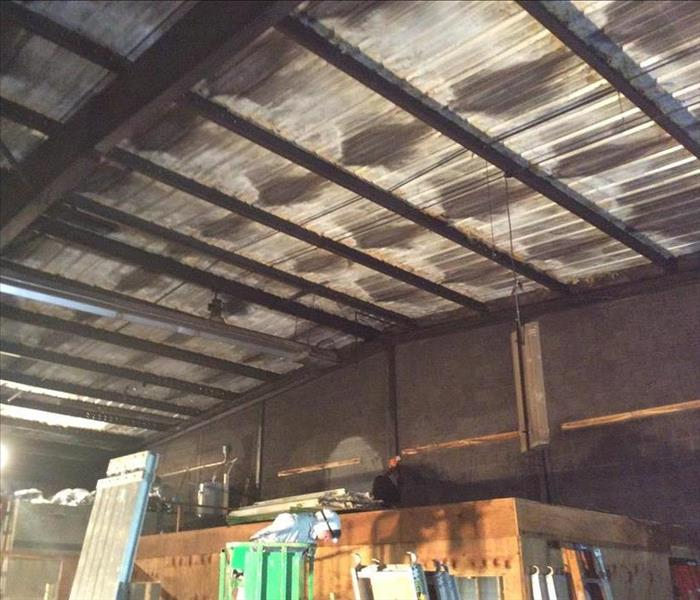 Soot-blackened warehouse ceiling and walls over the laundry room area.