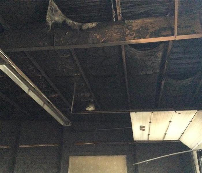 Warehouse ceiling, walls, and bay door blackened with fire and soot damage.