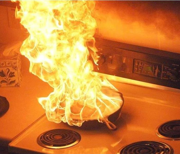 Fire-engulfed frying pan on an electric stove.