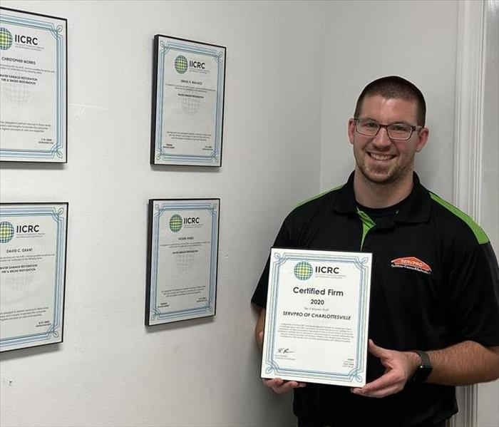 Production Manager, Ryan Mitchell, holding our IICRC Certified Firm plaque, next to the wall of employee certifications.