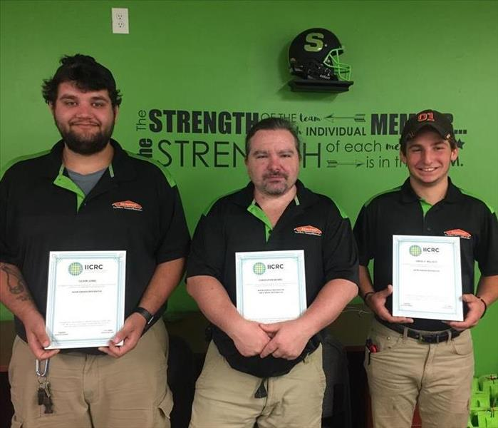 Three crew members each holding their certifications
