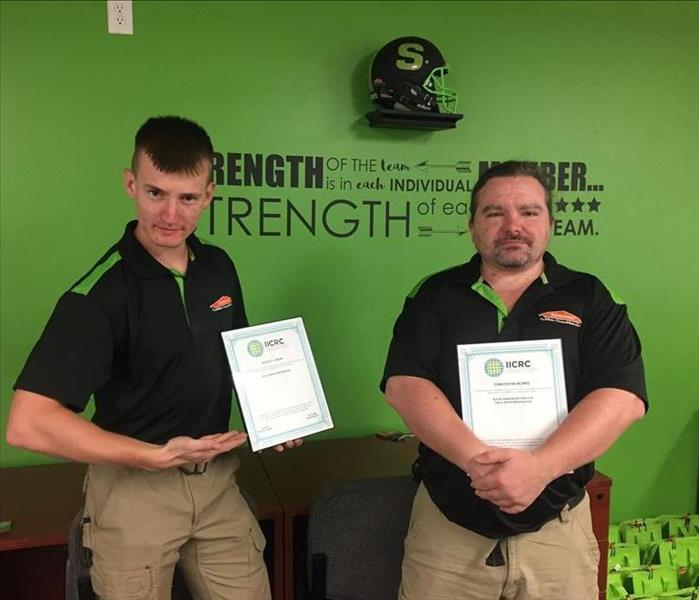 Two technicians making a silly pose while holding their certifications