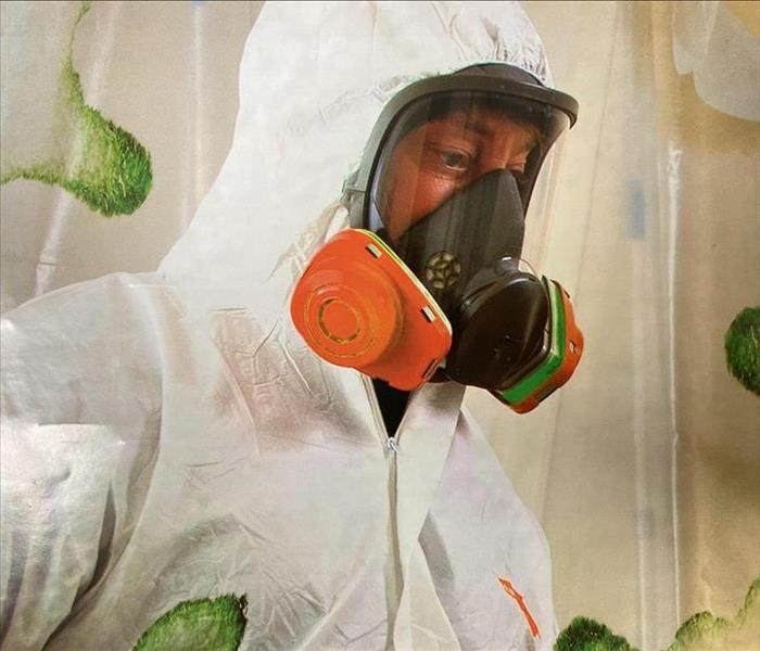 Man in white remediation suit with face mask and respirator, in a mold containment area.