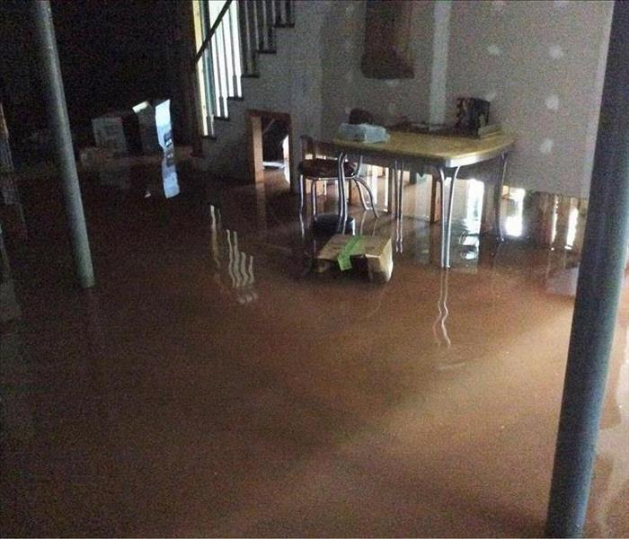 Dark, gloomy basement with storm water completely covering the floor.