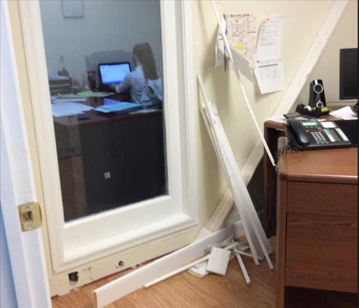 Water damaged office baseboards pulled up while office worker in next room.