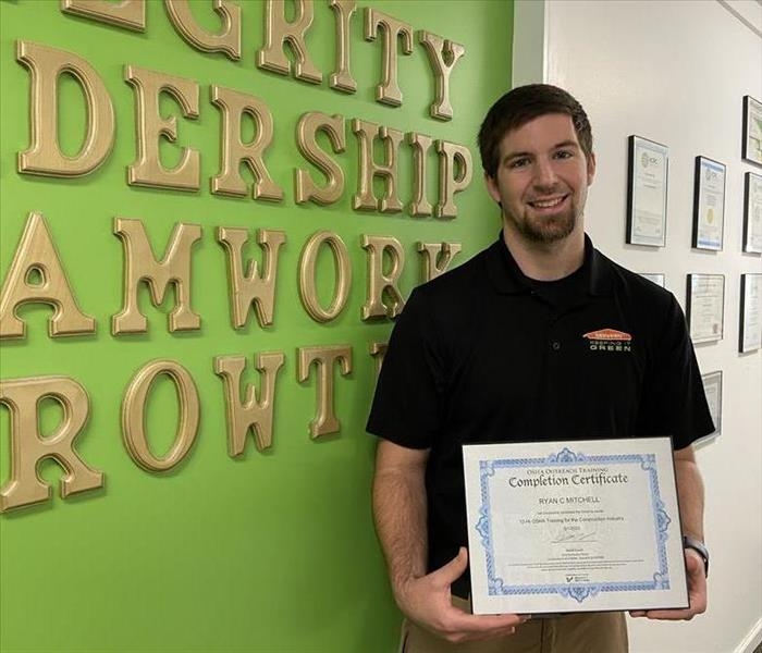 Production Manager, Ryan Mitchell, holding his OSHA-10 certification.
