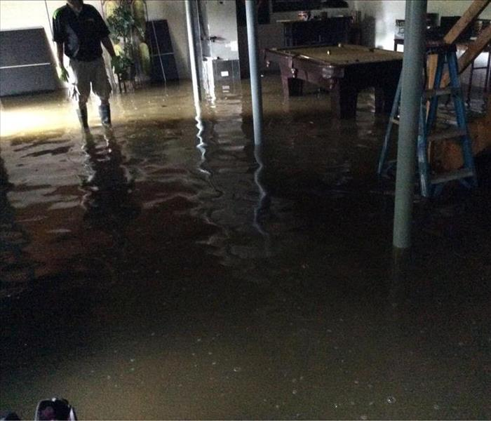 SERVPRO of Charlottesville team member, wearing rubber boots, standing in above ankle-deep water in flooded basement.