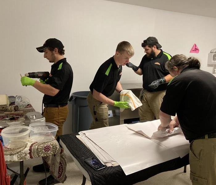 Four SERVPRO of Charlottesville technicians using the Ultrasonic machine to clean soot begrimed pack out items.